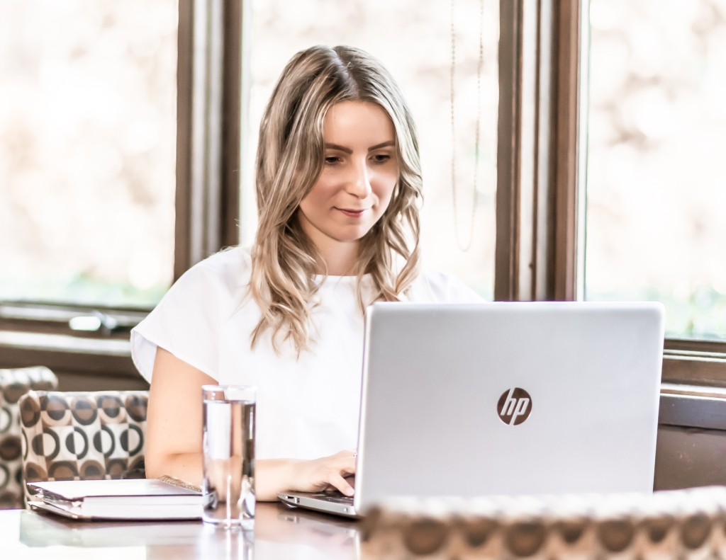 Woman working at a laptop in a cafe at a table